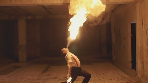Fire show artist breathe fire in the dark at abandon building, slow motion.