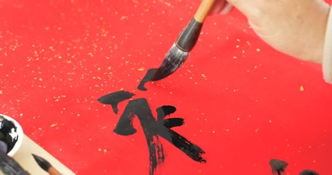 Writing chinese calligraphy with word meaning luck for lunar new year