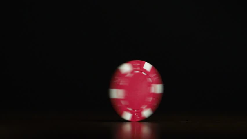Poker chip spinning on the table. Casino theme. Poker game, poker chips on table, on black background