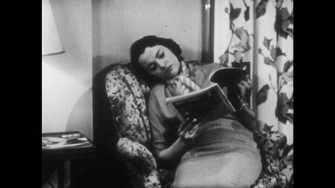 1950s: UNITED STATES: lady relaxes in chair. She flicks through magazine. Lady thinks to self. She yawns. She sleeps in chair.
