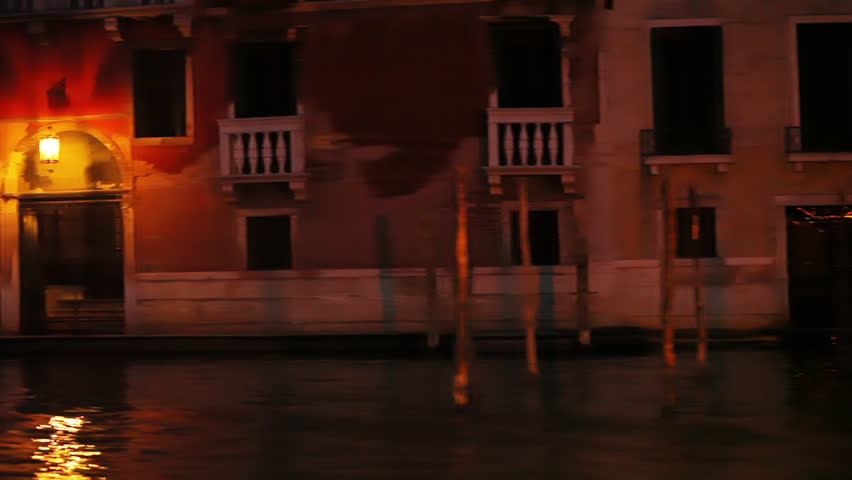 Passing a boat and a well lit lamp post in a Venice waterway