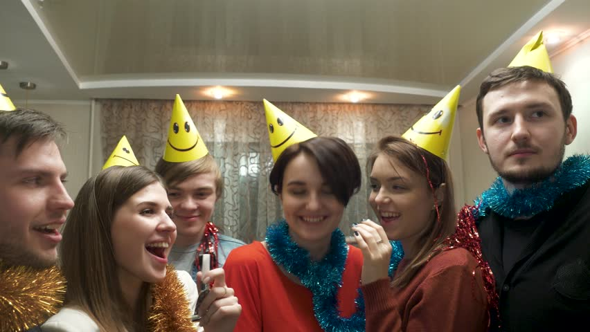 Friends with party hat blowing and having fun.