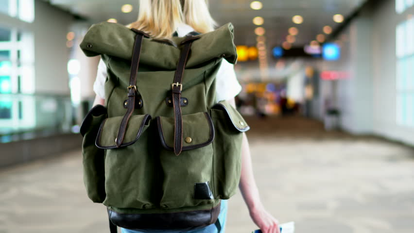 Young female traveler hurrying for check in airport walking hall, back view of tourist with backpack crossing terminal for registration