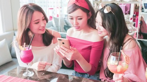 happy woman friends use phone and chatting in restaurant