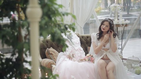 A young girl in lingerie and negligee sits on the couch and dresses pearl earrings