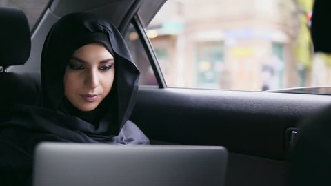 Portrait of young attractive muslim woman in hijab sitting on the back seat in taxi and using her laptop. Slowmotion shot