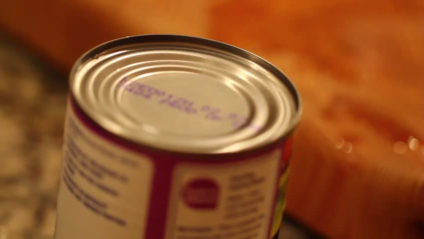 opening a can of beans with a can opener