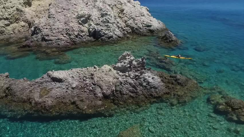 Summer chilling! chill vibes on a greek holiday. Beautiful drone shot of a colorful sea kayak exploring a series of rock formations on an authentic adventure in the Mediterranean. Fun & epic vacation