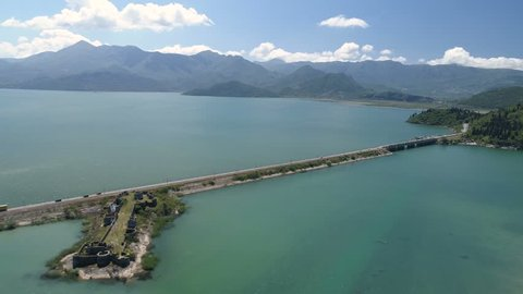 Aerial view at the dam with railroad and vehicular bridge leading through the Skadar lake. Route from Podgorica to Adriatic coast.