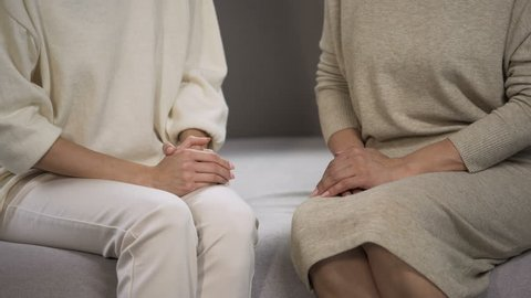 Young lady holding and stroking hand of senior woman, calming and supporting