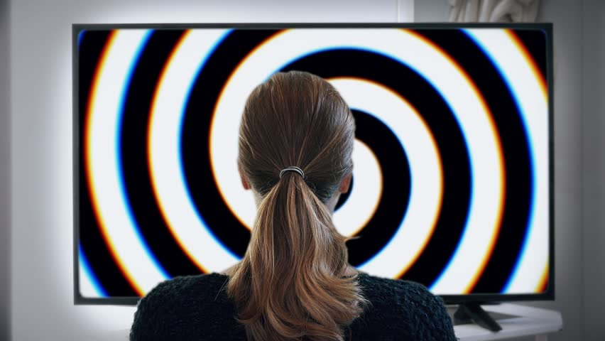 Watching TV Girl Gets Hypnotized With Images. Young woman hypnotized by big screen television. Shot behind model shoulders. | Shutterstock HD Video #34541317