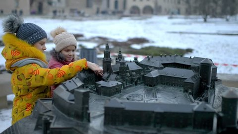 KRAKOW, POLAND - JANUARY 9 2016: Two little beautiful girls walk in Wawel, is fortified architectural complex erected on left bank of Vistula river.