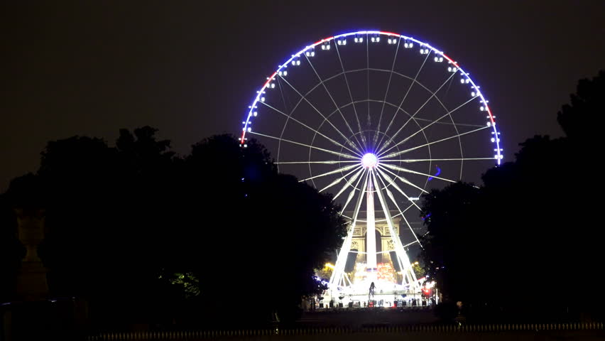 A ferris wheel (Roue de Paris) on the Place de la Concorde at night from the Tuileries Garden in Paris. It was first installed for the 2000 millennium celebrations