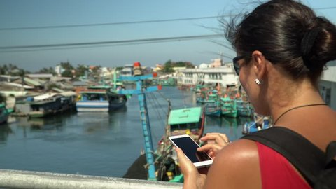 A girl using a smartphone at seaside,boat sailing in the harbour. Hands with phone. Close up. Sunny day in Vietnam. Vietnam