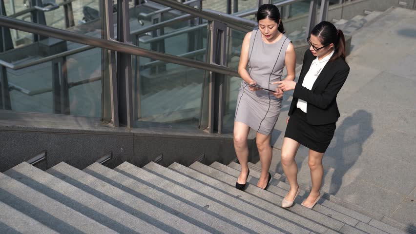 Two Asian women talking about business with holding digital tablet while walking up stairs outside of office building