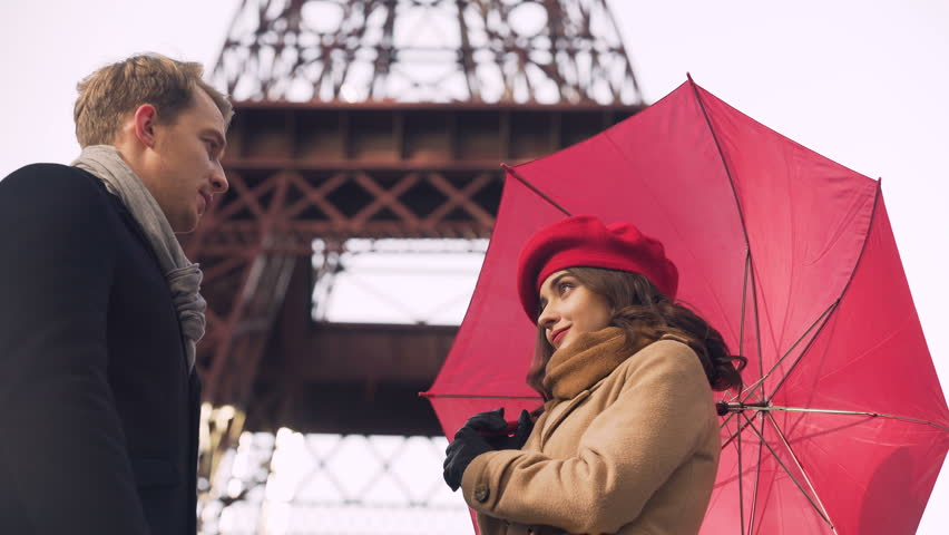 Beautiful young couple tenderly kissing under umbrella, romantic date in Paris | Shutterstock HD Video #34590997