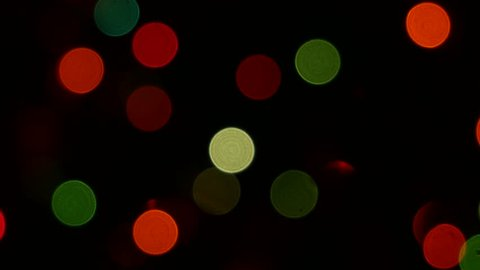 Defocused holiday lights. 4k footage. Bokeh particles floating. Motion background animation. Abstract Blurred Christmas Lights Bokeh Background. Blinking Christmas Tree Lights Twinkling.