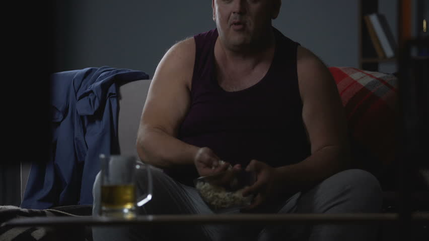 Man watching TV with popcorn and beer, messy careless lifestyle, food addiction