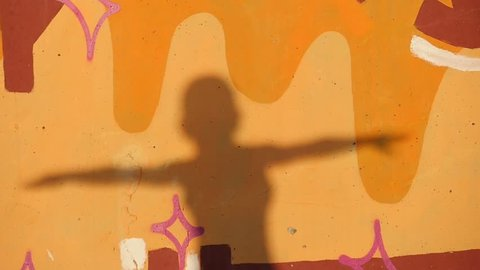 moving silhouette of a little boy with raised hands on the wall with colorful graffiti at sunset