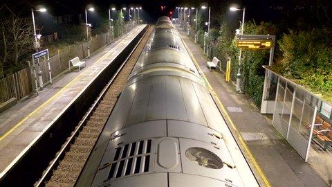 overground train leave platform at night united kingdom