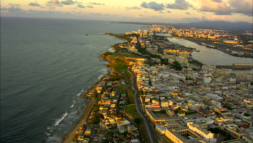 Aerial coastal sunset view of San Juan city harbor ferry terminal and cruise Port hotel and condominium resorts Puerto Rico Caribbean
