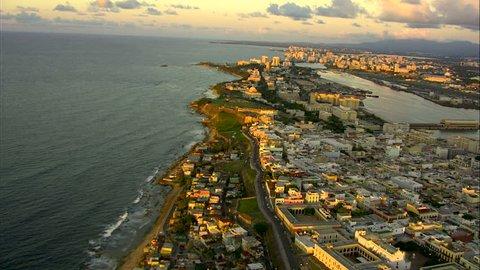 Aerial coastal sunset view of San Juan city harbor ferry terminal and cruise Port hotel and condominium resorts Puerto Rico Caribbean