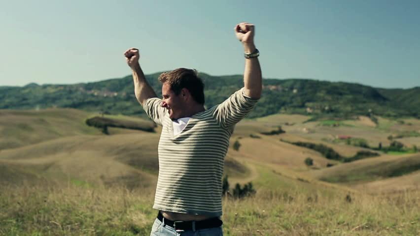 Young man enjoying panoramic view of Tuscany, crane shot
