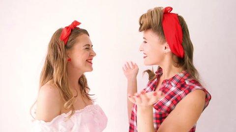 two girls in pin-up style talk, tell gossips, whisper