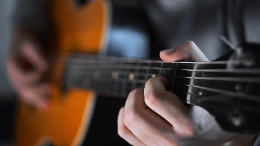 Guitar player plays random chords on the acoustic western guitar with steel strings ,exercises and arpeggios, video with sound, plaing the guitar, muscial instrument   Shutterstock HD Video #34637647