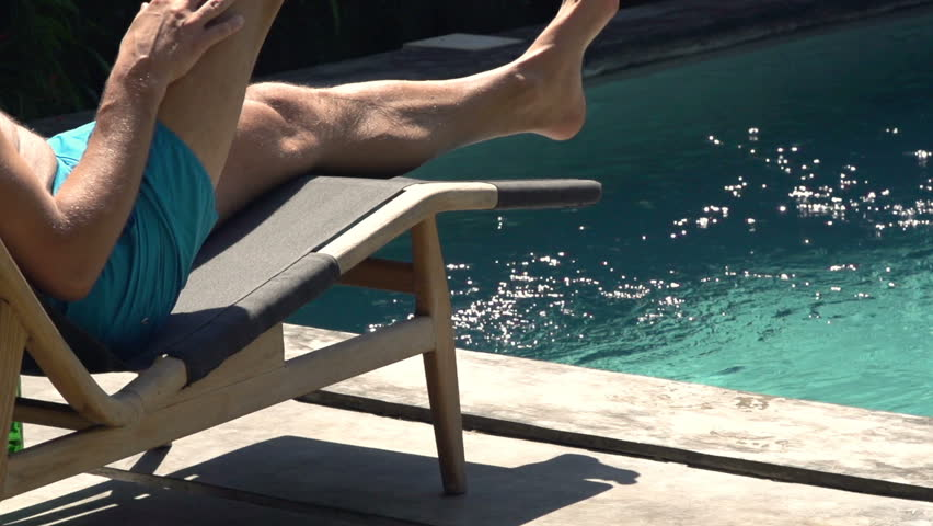 Man relaxing on sunbed lying by swimming pool