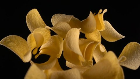 potato chips in free fall on a black background