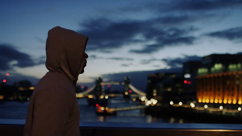 Profile steadicam shot of a hooded male athlete jogging in the city early morning, in slow motion