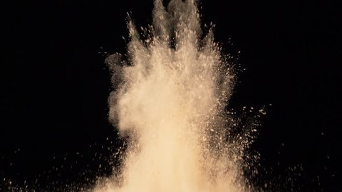 bright yellow powder explosion on black background