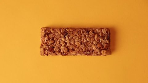 Stop motion of granola bars rotation on a yellow background