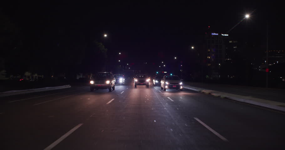 Night Process plate master straight back begins left turn two motorcycle cops behind onto city street lined businesses some apartments We stop lane Other angles