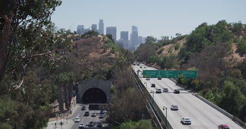 Day Shot begins down freeway cars driving we see signs stating downtown Dodger stadium Los Angeles skyline We see tunnel down below car's coming camera