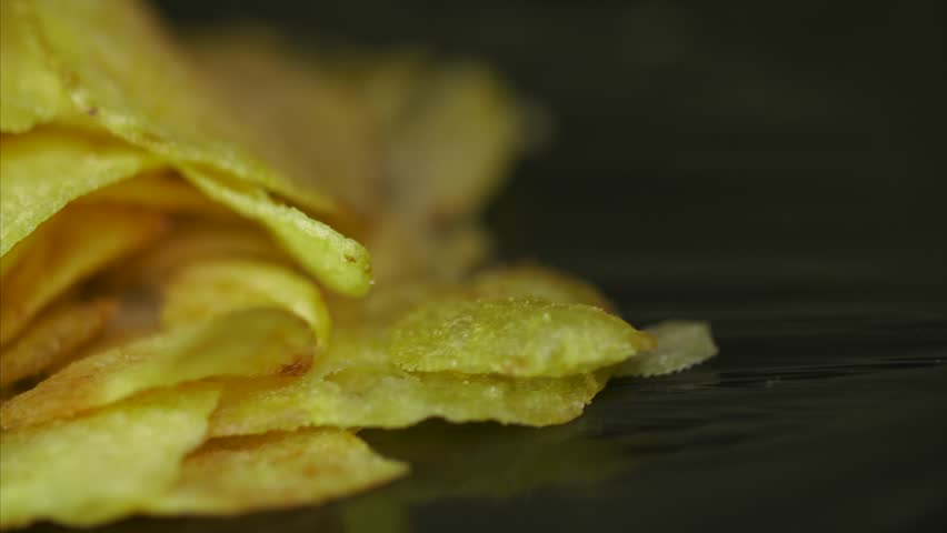 Potato Chips Rotating On Black Background. Potato chips are rotated on a black background. Close-up of yellow delicious chips randomly lying on a table. Excellent Footage for themes: Harmful food | Shutterstock HD Video #34690927
