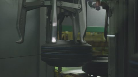 closeup circular mechanism with large hooks rotating rubber tires completes tyre production process