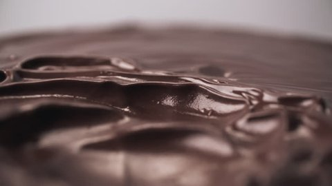 Melted chocolate blow waves full HD extreme close-up slow motion video. Hot cocoa topping glaze splashing flowing moving. Liquid tasty sweet dessert cooking