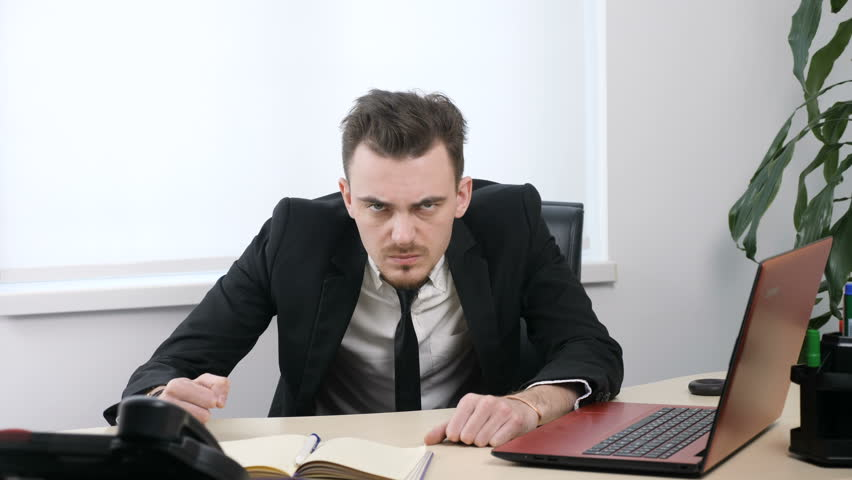 Young angry businessman in suit is sitting in office and showing No by shaking head, gesture 60 fps