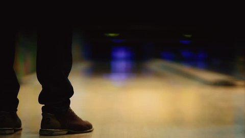 In the game club for bowling, the player throws a bowling ball that knocks down skittles. Smooth movement of the focus, from the front to the back.