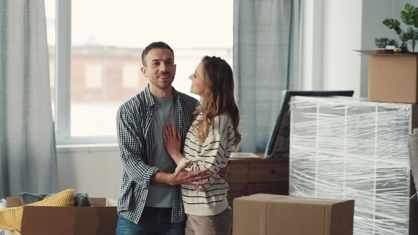 Husband and wife going into new apartment. People in casual clothes bringing cardboard boxes with things to spacious room. Spaniel rejoicing at arrival of owners. Hugging. | Shutterstock HD Video #34760737