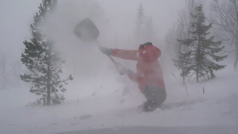 A man shoveling snow during a heavy storm in the Swedish mountains