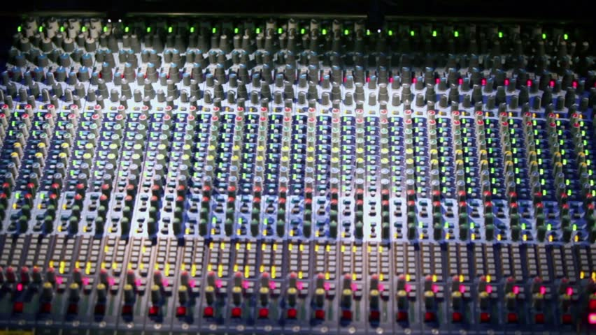 Professional audio mixer runs with illumination and many knobs, shown in motion