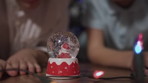 Close-up Two children shook the snow globe, put it on the floor and peep inside it as the snow falls on the santa claus located inside this snow globe slow motion