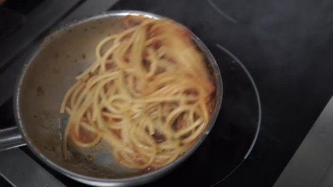 The chef prepares an Italian pasta spaghetti in a restaurant. Italian Spaghetti in sauce with meatballs. Italian cuisine.