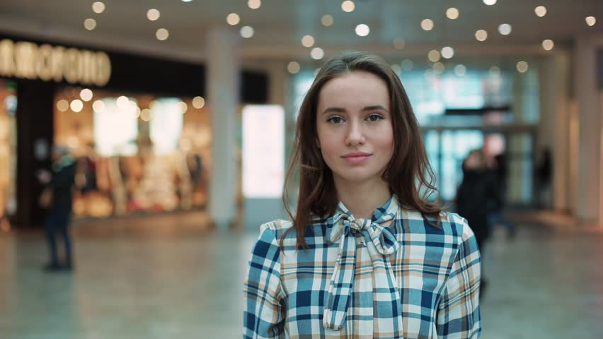 Cute young beautiful woman look at camera smiling feel happy in mall close up shopaholic clothing fashion person girl shopping money lifestyle store portrait weekend shop slow motion