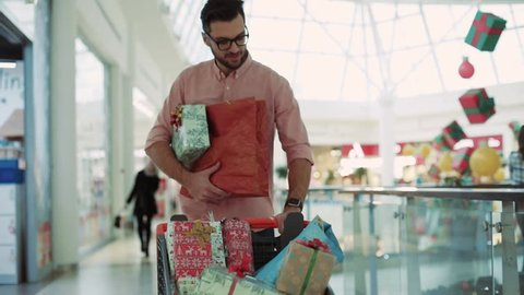 Close-up of an attractive man with Christmas presents in a hurry at a mall smiling looking at a clock christmas family christmas decorations design tree love portrait slow motion