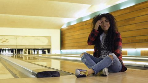 Pretty woman throws bowling ball and falls down on the path