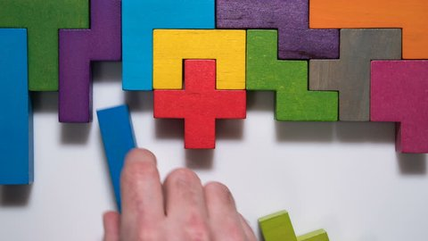 Top view on man's hand folding colorful wooden blocks on the white table background, timelapse. The concept of logical thinking.